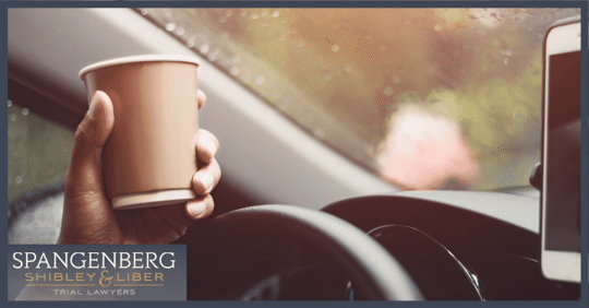 driver holding a cup of coffee while driving distracted